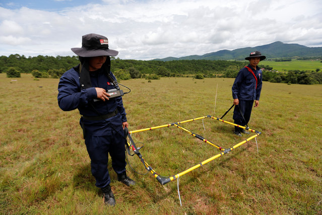 Technicians from the NGO Mines Advisory Group (MAG) work in a field searching for unexploded bombs that were dropped by the U.S. Air Force planes during the Vietnam War, at Phaxay district in Xieng Khouang province, Laos September 2, 2016. (Photo by Jorge Silva/Reuters)