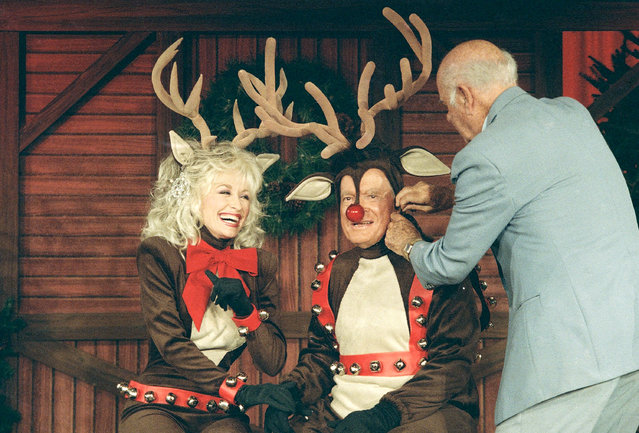 Comedian Bob Hope has his costume adjusted while on the set with entertainer Dolly Parton, Sunday, December 12, 1988 in Miami, Fla. during taping for Bob Hope's Christmas Special aboard the luxury cruise liner Royal Vikings Sun in the Port of Miami. The pair appears in a vignette dressed as reindeer. Hope's Christmas Special will be aired on December 17, on NBC television. (Photo by Kathy Willens/AP Photo)