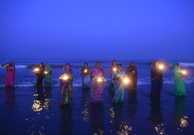 Hindu devotees pray while standing in the waters of the Arabian Sea as they worship the Sun god Surya during the Hindu religious festival Chatt Puja in Mumbai October 30, 2014. (Photo by Danish Siddiqui/Reuters)