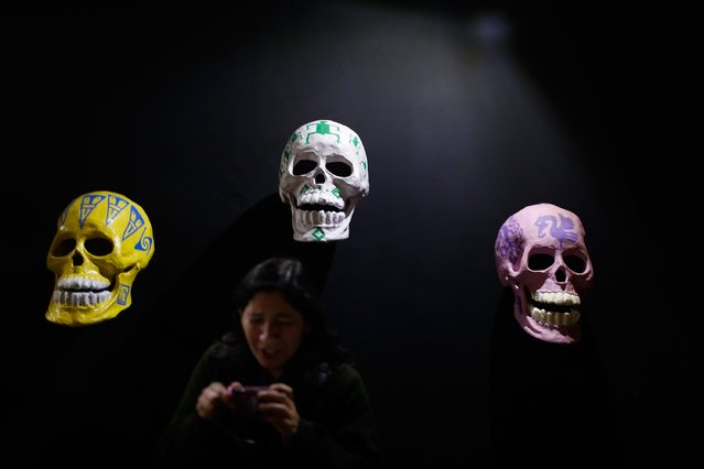 A woman checks a picture on her camera while standing in front of skulls, which form part of an art installation to celebrate the Day of the Dead, in Zocalo Square, Mexico City, October 30, 2014. (Photo by Tomas Bravo/Reuters)