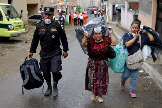 A policeman escorts two women, who are looking for missing relatives, away from an area affected by a mudslide, in Santa Catarina Pinula, on the outskirts of Guatemala City, October 4, 2015. Guatemalan authorities on Sunday said that around 300 people remain missing after a massive landslide on Thursday night claimed at least 87 lives and flattened over a hundred homes. (Photo by Josue Decavele/Reuters)