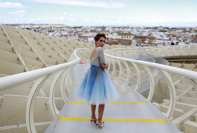 Spanish model, Angela Cristina, 27, stands on the footbridge of the wooden structure Metropol Parasol as she wears a creation by Francisco Tamaral during an urban photo shooting, part of the Andalucia de Moda (Andalusia Fashion) in Seville, southern Spain, November 4, 2014. (Photo by Marcelo del Pozo/Reuters)