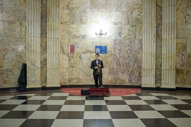 In the Teatralnaya station, Yuri plays a concerto. He had to audition to play in one of the 15 authorized stations. Each year, 200 people are selected out of 1,000 applicants, according to a representative of Moscow's metro. (Photo by Didier Bizet/The Washington Post)