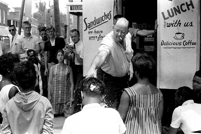 Robert Fahsenfeldt, owner of a segregated lunchroom in the racially tense Eastern Shore community of Cambridge, Maryland, douses a white integrationist with water, on July 8, 1963. The integrationist, Edward Dickerson, was among three white and eight African American protesters who knelt on the sidewalk in front of the restaurant to sing freedom songs. A raw egg, which Fahsenfeldt had broken over Dickerson's head moments earlier, still is visible on the back of Dickerson's head. The protesters were later arrested. (Photo by William A. Smith/AP Photo)