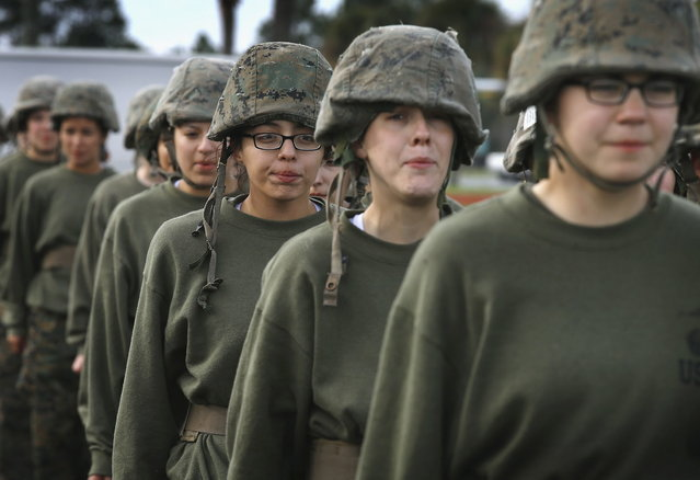 Female Marine recruits get into formation following hand-to-hand combat training during boot camp February 27, 2013 at MCRD Parris Island, South Carolina. Female enlisted Marines have gone through recruit training at the base since 1949. About 11 percent of female recruits who arrive at the boot camp fail to complete the training, which can be physically and mentally demanding. On January 24, 2013 Secretary of Defense Leon Panetta rescinded an order, which had been in place since 1994, that restricted women from being attached to ground combat units. About six percent of enlisted Marines are female. (Photo by Scott Olson/AFP Photo)