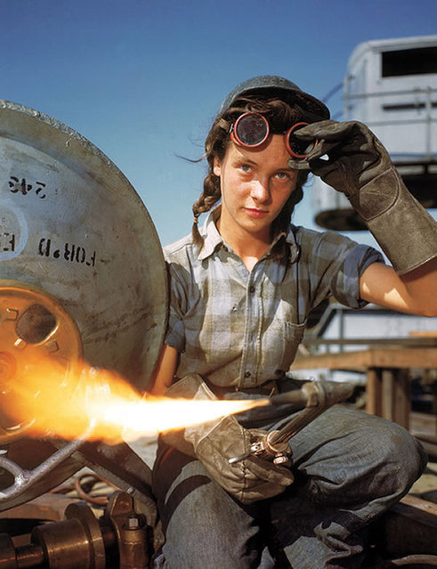 A welder at a boat-and-sub-building yard adjusts her goggles before resuming work, October, 1943. By 1945, women comprised well over a third of the civilian labor force (in 1940, it was closer to a quarter) and millions of those jobs were filled in factories: building bombers, manufacturing munitions, welding, drilling and riveting for the war effort. (Photo by Bernard Hoffma/Time & Life Pictures)