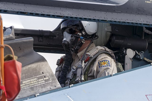 A pilot sits in the cockpit of a Sukhoi Su-30 fighter jet at the Hmeymim air base near Latakia, Syria, in this handout photograph released by Russia's Defence Ministry October 22, 2015. (Photo by Reuters/Ministry of Defence of the Russian Federation)