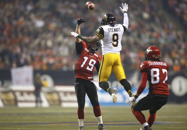 Calgary Stampeders' quarterback Bo Levi Mitchell attempts a pass over Hamilton Tiger Cats' Brandon Stewart as teammate Simon Charbonneau-Campeau watches during the second half of the CFL's 102nd Grey Cup football championship in Vancouver, British Columbia, November 30, 2014. (Photo by Ben Nelms/Reuters)