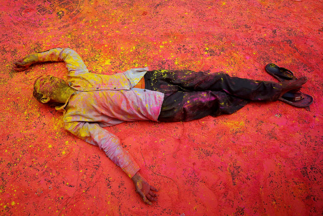 A Hindu devotee, smeared in coloured powder, takes a rest on a road during a procession for Holi celebrations in Kolkata, India, February 28, 2018. (Photo by Rupak De Chowdhuri/Reuters)
