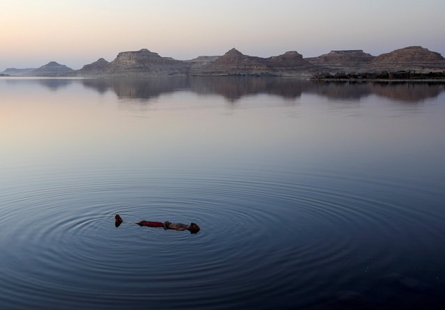 """An Egyptian man swims in a lake in front of Taghaghien Island Resort in Egypt's Western Desert, during the activation of domestic tourism after the government cancelled the celebration of the Siyaha peace festival, or the """"Peace festival"""", amid concerns over the coronavirus disease (COVID-19) pandemic, in Siwa Oasis, west of the Egyptian capital, Egypt October 16, 2020. (Photo by Amr Abdallah Dalsh/Reuters)"""