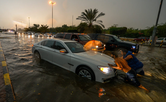 People try to push a car at a flooded street in Salmiya, Kuwait, 28 October 2015. A thunderstorm hit Kuwait on 28 October disrupting schools and universities and flooding some roads. (Photo by Raed Qutena/EPA)