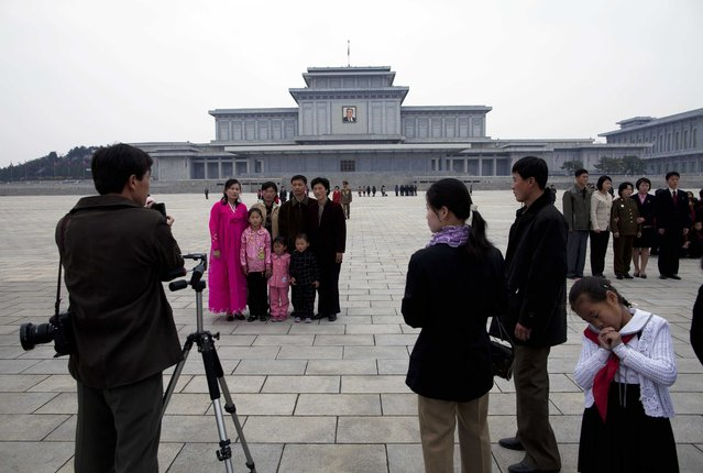 In this April 15, 2011 photo, families have their photographs taken in front of the Kumsusan Memorial Palace in Pyongyang, North Korea. The palace, which was the official residence of Kim Il Sung until his death in 1994, is now a mausoleum where his embalmed body lies in state. (Photo by David Guttenfelder/AP Photo)