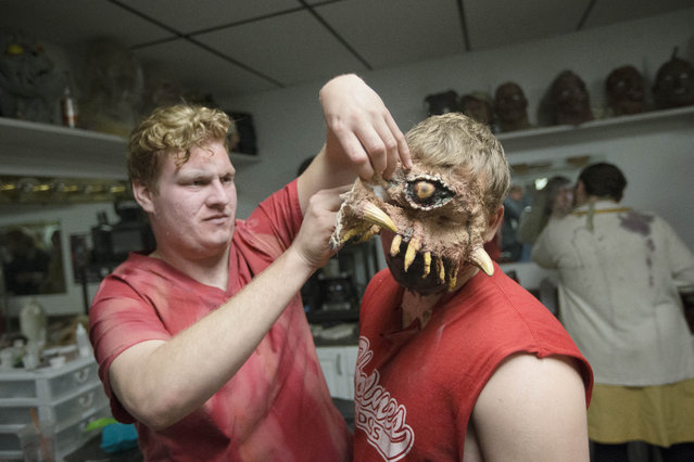 """Actor Matt Maloney, left, helps remove a prosthetic from the face of colleague Robert Hensley after closing at the The Dent Schoolhouse haunted attraction, Thursday, October 29, 2015, in Cincinnati. The haunt, owned and operated by Bud Stross, 28, and Josh Wells, two high school friends, inhabits a late 19th century schoolhouse they've renamed """"The Dent Schoolhouse"""". (Photo by John Minchillo/AP Photo)"""