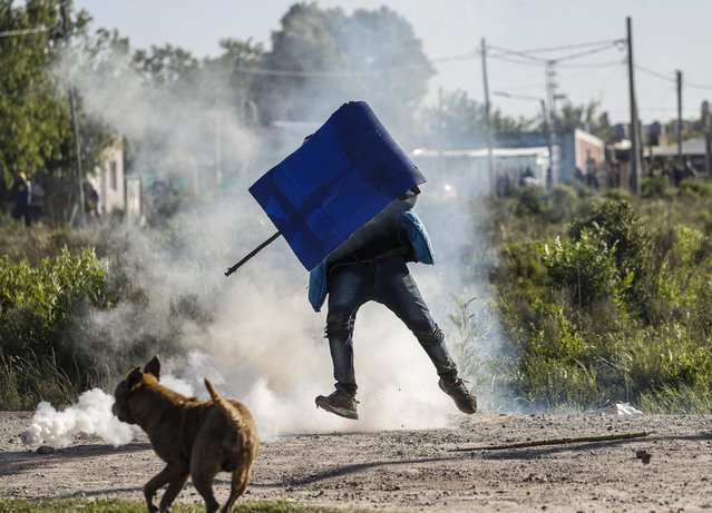 A man carries a makeshift shield through tear gas launched by police during an eviction at a squatters camp in Guernica, Buenos Aires province, Argentina, Thursday, October 29, 2020. (Photo by Natacha Pisarenko/AP Photo)