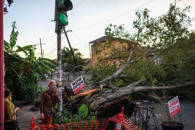 Olivia Mancing (L) and Zachery Quale talk outside of Flora Gallery and Coffee Shop near a downed tree in the street after Hurricane Zeta swept through New Orleans, Louisiana, U.S. October 29, 2020. (Photo by Kathleen Flynn/Reuters)