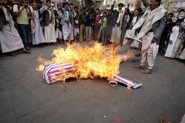 Members of the Yemeni al-Houthi Shiite rebel group burn an effigy of a U.S. aircraft during a demonstration to protest against the U.S. and Saudi interference in Yemen, after Friday prayer in Sanaa, Yemen, Friday, April 12, 2013. (Photo by Hani Mohammed/AP Photo)