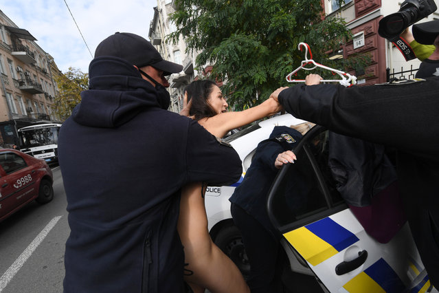 Police officers detain a FEMEN naked activist during an action at the Poland embassy in Kiev on October 26, 2020 in support of Polish women in their right to abortion. (Photo by Sergei Supinsky/AFP Photo)