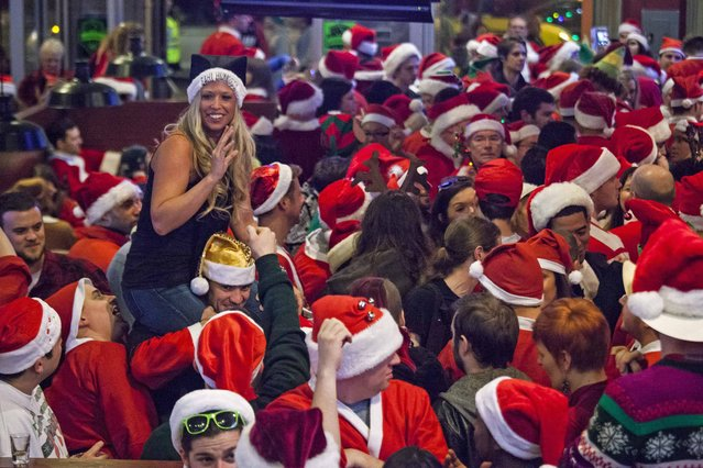Santarchy participants fill Gameworks in Seattle, Washington December 13, 2014. Santarchy, an annual event in Seattle, drew hundreds to local bars in celebration of Christmas and inebriation. (Photo by David Ryder/Reuters)