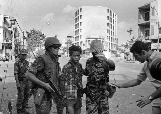South Vietnamese forces escort suspected Viet Cong officer Nguyen Van Lem (also known as Bay Lop) on a Saigon street February 1, 1968, early in the Tet Offensive. Moments later, Lem was executed by Gen. Nguyen Ngoc Loan, chief of the national police. (Photo by Eddie Adams/AP Photo)