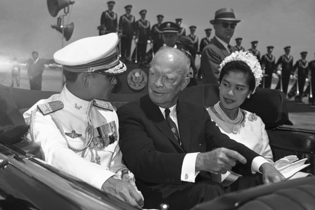 In this June 28, 1960, file photo, U.S. President Dwight Eisenhower, center, is seated between Thailand's King Bhumibol Adulyadej, left, and Queen Sirikit for a motorcade drive from National Airport to the White House in Washington.  (Photo by AP Photo)