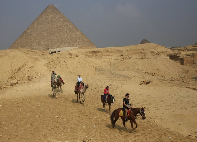 Tourists ride horses in front of the Giza pyramids on the outskirts of Cairo, Egypt, November 8, 2015. (Photo by Amr Abdallah Dalsh/Reuters)