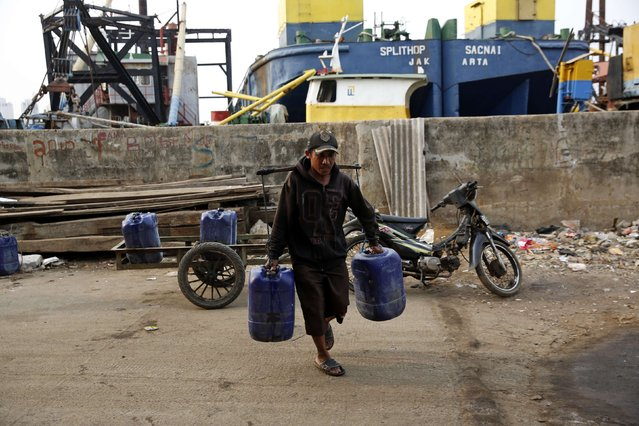 A man delivers clean water to residents living next to the sea wall in Muara Baru, north Jakarta, October 7, 2014. (Photo by Darren Whiteside/Reuters)