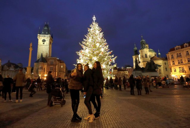 People gather by a Christmas tree illuminating the Old Town Square in Prague, Czech Republic, Saturday, November 28, 2020. Prague city hall has lit up the Christmas Tre but cancelled the traditional Christmas markets due to a record surge in coronavirus infections. (Photo by Petr David Josek/AP Photo)