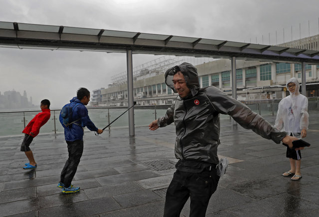 People play with strong wind caused by Typhoon Haima on the waterfront of Victoria Habour in Hong Kong, Friday, October 21, 2016. (Photo by Vincent Yu/AP Photo)
