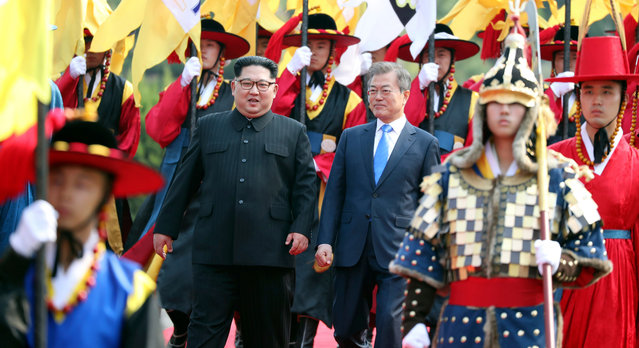 In this Friday, April 27, 2018, file photo, North Korean leader Kim Jong Un, left, and South Korean President Moon Jae-in, right, walk together through a honor guard at the border village of Panmunjom in the Demilitarized Zone. After their meeting at the borderline, Kim and Moon moved to a small plaza to inspect an honor guard before they walked together for a couple of minutes to Peace House, the venue for the summit. (Photo by Korea Summit Press Pool via AP Photo)