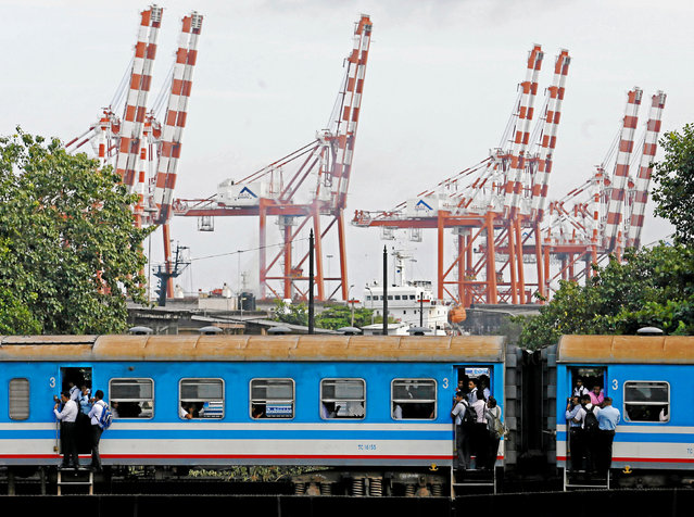 People travel in a train as it passes by the main shipping port in Colombo, Sri Lanka August 31, 2016. (Photo by Dinuka Liyanawatte/Reuters)