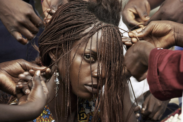 Polio sufferer Marie Diekese, 20, has her hair braided by other girls afflicted by the disease inside the International Polio Victim Response Committee (IPVRC) compound in Democratic Republic of Congo's capital Kinshasa November 24, 2006. (Photo by Finbarr O'Reilly/Reuters)