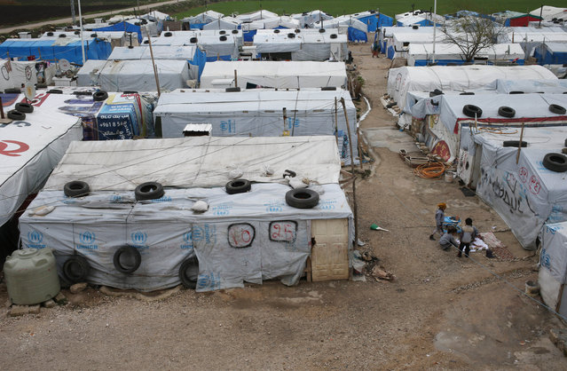 Syrian chilren gather outside their tents  at a refugee camp in Deir Zannoun village, Bekaa valley, Lebanon, Tuesday, January 6, 2015. A snow storm is expected to hit Lebanon affecting Syrian refugees, many of whom live in tents without heating. The government estimates there are about 1.5 million Syrians in Lebanon, about one-quarter of the total population. (Photo by Hussein Malla/AP Photo)