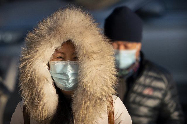 A woman wearing a face mask to protect against the spread of the coronavirus walks along a street during the morning rush hour in Beijing, Wednesday, December 30, 2020. Beijing has urged residents not to leave the city during the Lunar New Year holiday in February, implementing new restrictions and mass testings after several coronavirus infections last week. (Photo by Mark Schiefelbein/AP Photo)