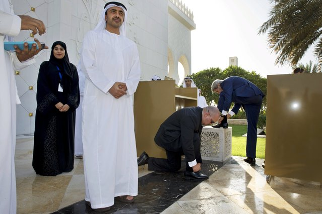 Emirati Foreign Minister Abdullah bin Zayed Al Nahyan (L) waits as U.S. Secretary of State John Kerry (R) and a member of diplomatic security tie their shoelaces after touring the Sheikh Zayed Grand Mosque in Abu Dhabi, United Arab Emirates, November 23, 2015. At far left is Hajar Alali, the mosque's cultural guide. (Photo by Jacquelyn Martin/Reuters)