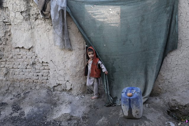 An internally displaced boy peers through the curtain of his temporary home in the city of Kabul, Afghanistan, Wednesday, December 30, 2020. Save the Children has warned that more than 300,000 Afghan children face freezing winter conditions that could lead to illness, in the worst cases death, without proper winter clothing and heating. (Photo by Rahmat Gul/AP Photo)