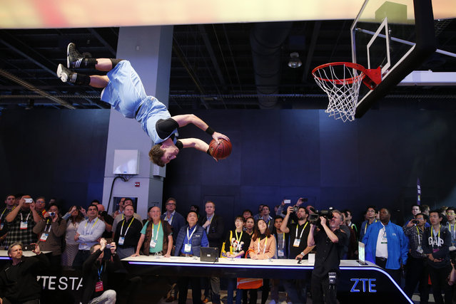 A basketball stunt performer makes a dunk off a trampoline at the ZTE booth during the International CES Wednesday, January 7, 2015, in Las Vegas. (Photo by John Locher/AP Photo)
