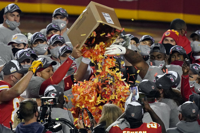 Kansas City Chiefs players dump a box of confetti on head coach Andy Reid after the AFC championship NFL football game against the Buffalo Bills, Sunday, Jan. 24, 2021, in Kansas City, Mo. The Chiefs won 38-24. (Photo by Jeff Roberson/AP Photo)