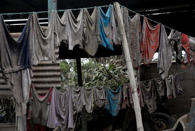 Clothes covered with ash hang on washing lines outside a house affected by the eruption of the Fuego volcano at San Miguel Los Lotes in Escuintla, Guatemala, June 7, 2018. (Photo by Carlos Jasso/Reuters)