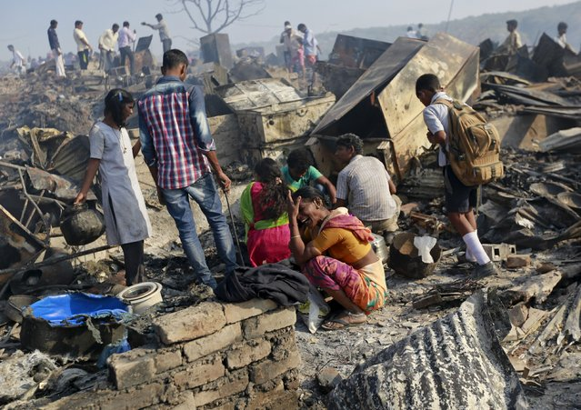 A woman cries as she sits on debris from her gutted hut after a fire occurred in a slum area in Mumbai, India, December 7, 2015. (Photo by Danish Siddiqui/Reuters)