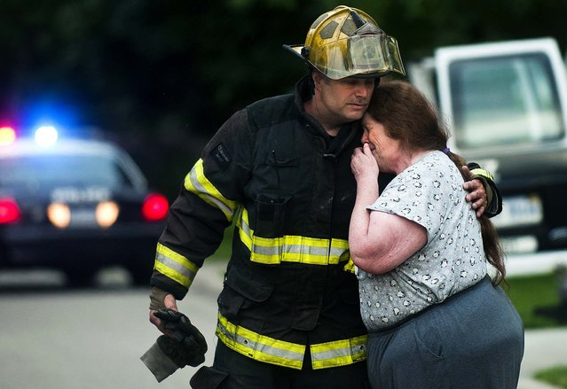 Grand Blanc firefighter Brad Hutchison consoles Wanda McCann after he informed her that her friend and neighbor was killed in a house fire Tuesday morning in Grand Blanc Township, Michigan, on June 25, 2013.  Police and firefighters tried to rescue a woman in her early 60s, but were unable to enter the home because of heavy smoke. It is the township's first fatal fire in about seven or eight years, said fire chief Jim Harmes. (Photo by Jake May/The Flint Journal)