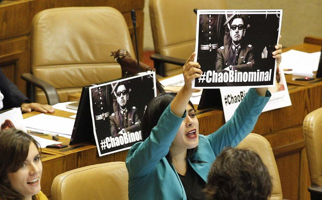 Communist Party deputy Karol Cariola, holds up a banner with the image of former dictator Augusto Pinochet, inside the congress, after a vote to reform the binomial voting system, in Valparaiso city, Northwest of Santigo January 20, 2015. (Photo by Rodrigo Garrido/Reuters)