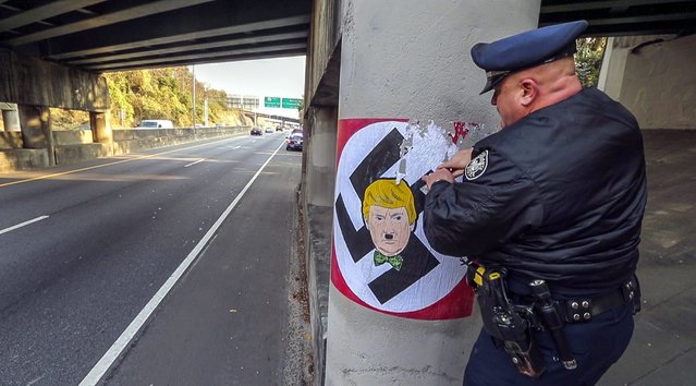 A photo provided by the Atlanta Journal-Constitution shows Atlanta police officer T. R. Coxe removing painted material of a large swastika featuring a likeness of Republican presidential candidate, Donald Trump, along the northbound Buford Highway Connector just south of the Piedmont exit, in Atlanta, Georgia, USA, 09 December 2015. Just days after Donald Trump's call to ban Muslims from entering the United States, someone painted large swastikas featuring the Republican presidential candidate's face on at least two northeast Atlanta bridge supports. (Photo by John Spink/EPA/AJC)