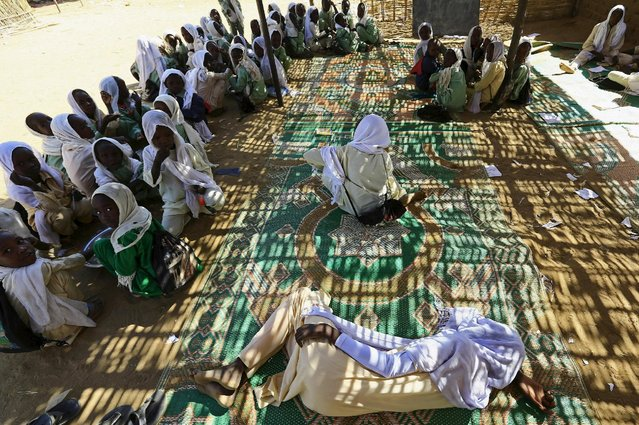 Internally displaced girls rest under a bamboo shade while their schoolmates receive meals provided through the school feeding program by the World Food Program at the Abushok camp in El Fasher in North Darfur, Sudan, November 17, 2015. (Photo by Mohamed Nureldin Abdallah/Reuters)