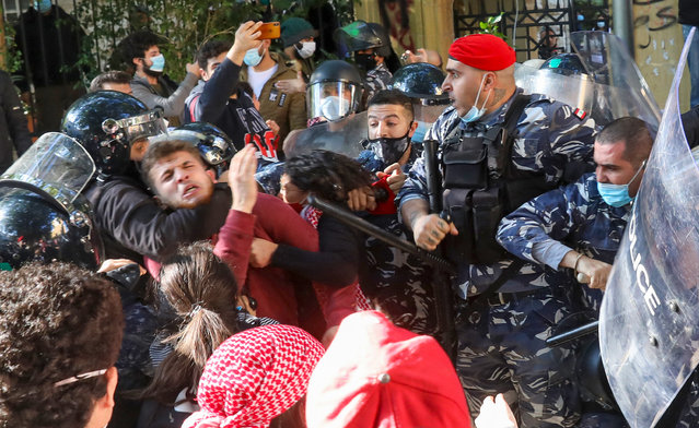 A policeman chokes a protester during clashes following a demonstration outside the entrance of the American University of Beirut, in the Lebanese capital's Bliss street on December 29, 2020, against the decision by a number of universities to adopt a new dollar exchange rate to price tuition. (Photo by Anwar Amro/AFP Photo)