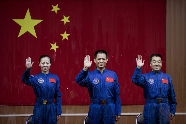 Chinese astronauts from left, Wang Yaping, Nie Haisheng and Zhang Xiaoguang wave from behind a glass enclosure as they arrive to meet the press at the Jiuquan satellite launch center, on June 10, 2013. (Photo by Andy Wong/AP Photo via The Atlantic)