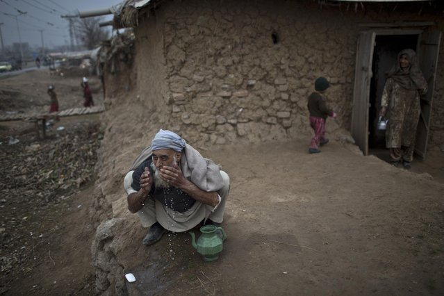 An elderly Afghan refugee man performs his wado, or cleaning himself before praying, outside his mud house in a slum on the outskirts of Islamabad, Pakistan, Wednesday, January 21, 2015. (Photo by Muhammed Muheisen/AP Photo)