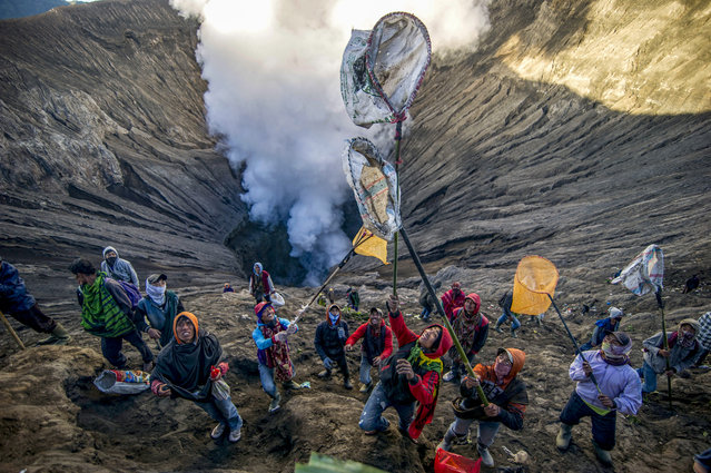 Some people prepare to catch offerings thrown by Tengger tribe people into the crater of Bromo volcano to in Probolinggo, East Java province, on June 30, 2018, as part of Yadnya Kasada festival which falls on the 14th day of the Kasada month based on the traditional Hindu lunar calendar. (Photo by Juni Kriswanto/AFP Photo)