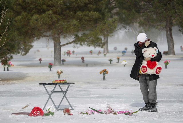 Antonio Cervantes brings gifts to the grave of his wife Gabriela, who died of the coronavirus disease (COVID-19), for Valentine's Day, at a cemetery in Santa Teresa, New Mexico, U.S., February 14, 2021. (Photo by Jose Luis Gonzalez/Reuters)