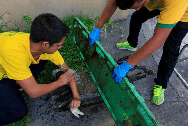Comandos de Salvamento rescuers wash blood off a stretcher after attending to a suspected gang member who was shot near the Comandos de Salvamento base in San Salvador, El Salvador August 15, 2016. (Photo by Jose Cabezas/Reuters)