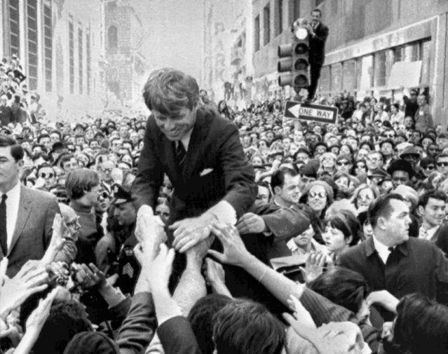 """In this April 2, 1968 file photo U.S. Sen. Robert F. Kennedy, D-NY, shakes hands with people in a crowd while campaigning for the Democratic party's presidential nomination on a street corner, in Philadelphia. Nearly 50 years after Robert F. Kennedy's assassination, a new documentary series on his life and transformation into a liberal hero is coming to Netflix. """"Bobby Kennedy for President"""" produced by RadicalMedia, Trilogy Films and LooksFilm launches Friday, April 27, 2018, on Netflix. (Photo by Warren Winterbottom/AP Photo)"""